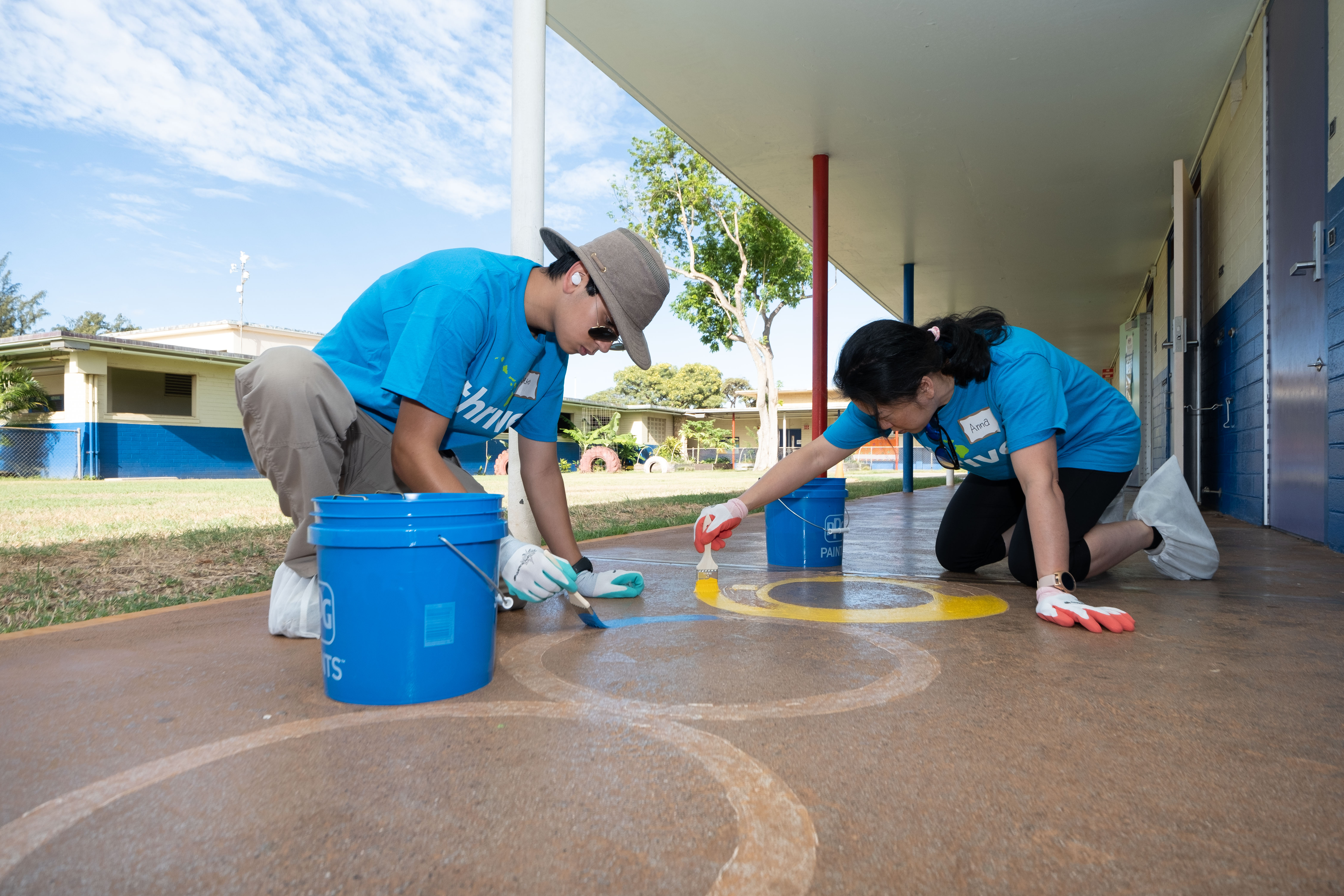 2 individuals kneeling down and repainting designs on the walkway outside of classrooms