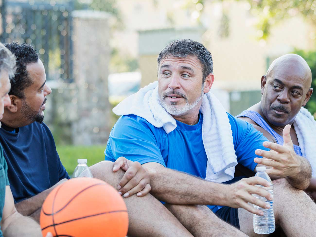 4 men on an outdoor basketball court sitting and talking