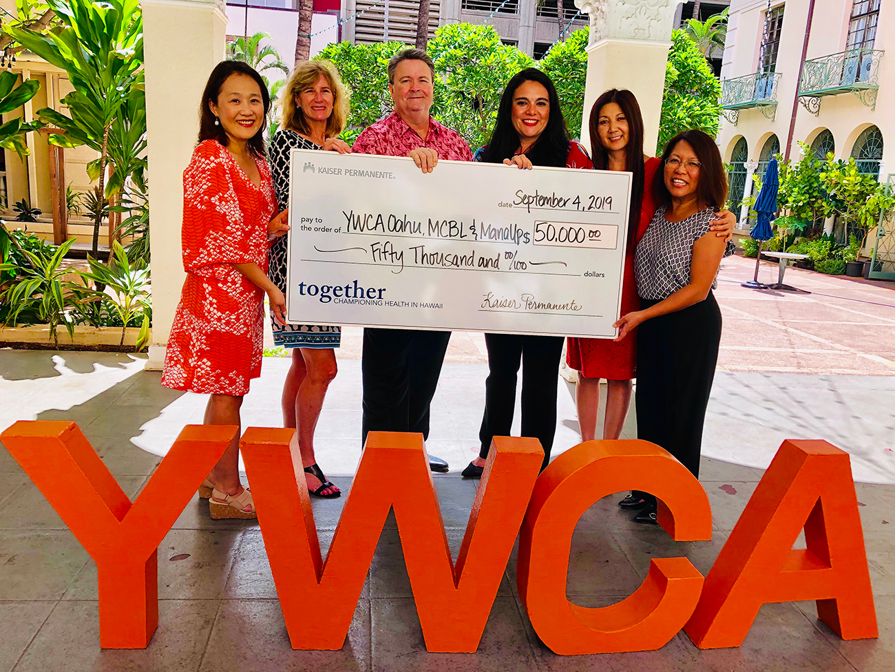 Group of 5 individuals standing by a YWCA sign and holding a giant check representing a grant from Kaiser Permanente