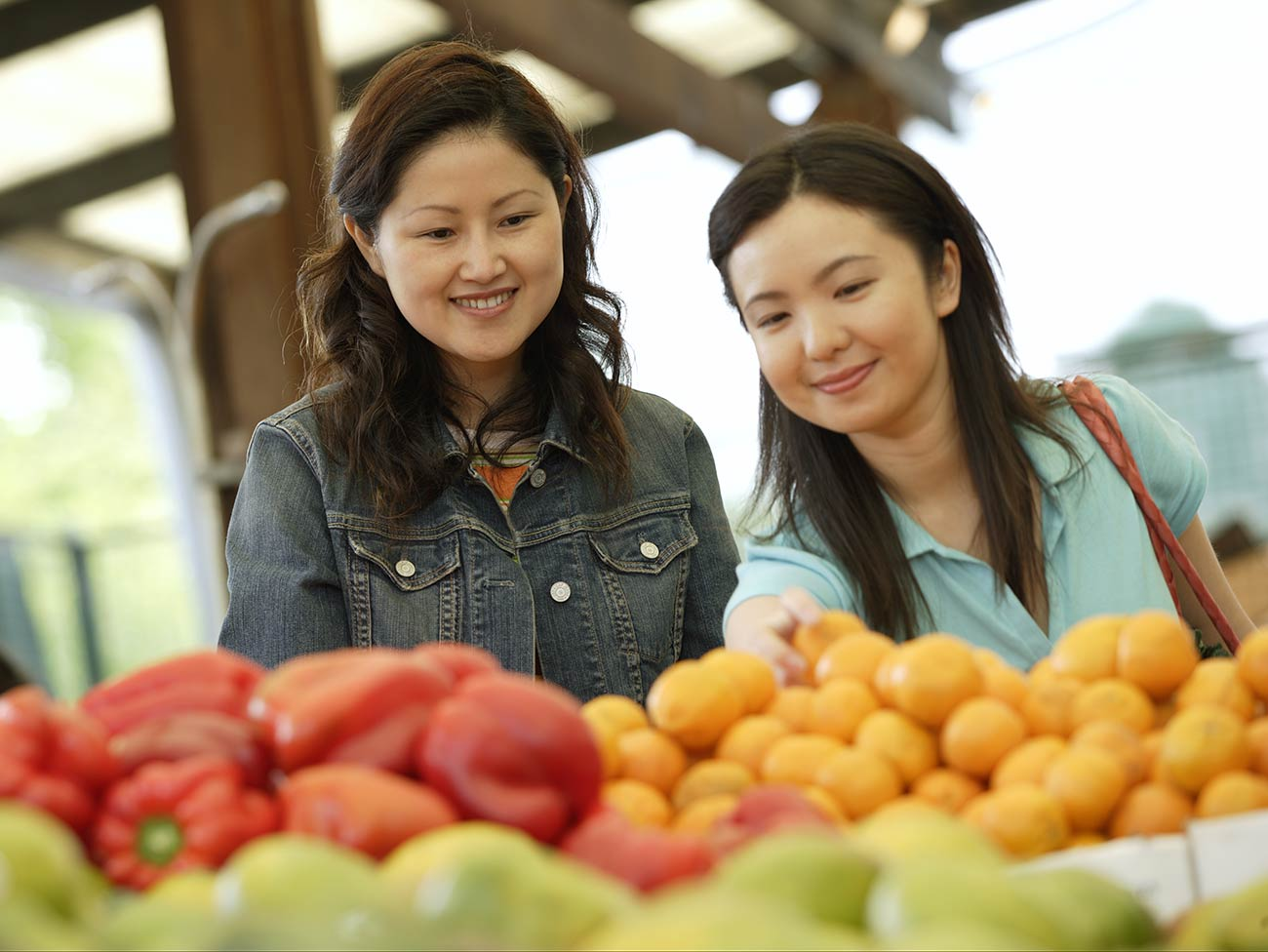 2 women selecting fruit at a farmers market