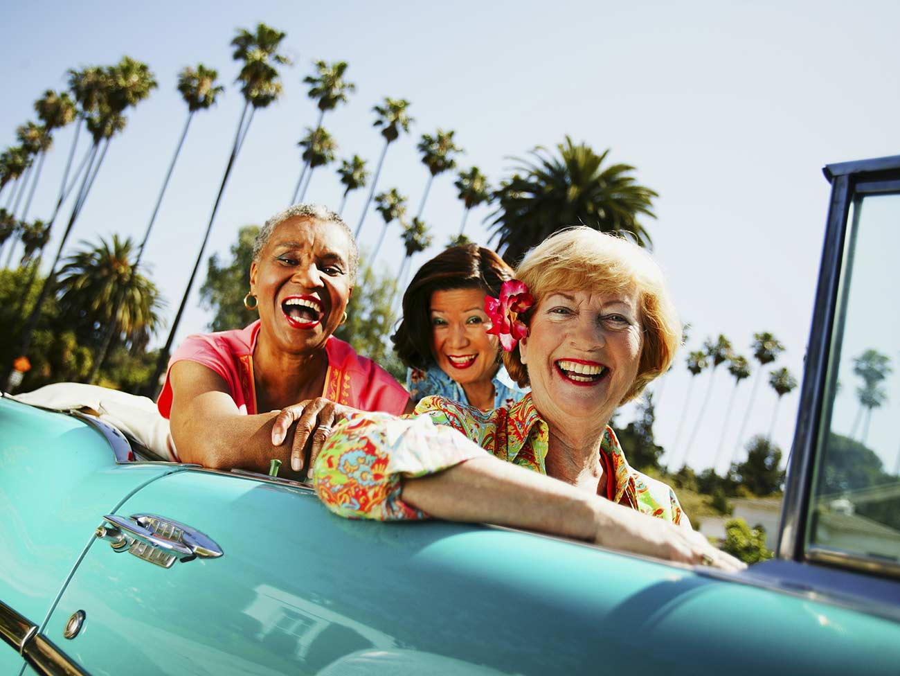 3 older women seated in a classic car with palm trees in the background