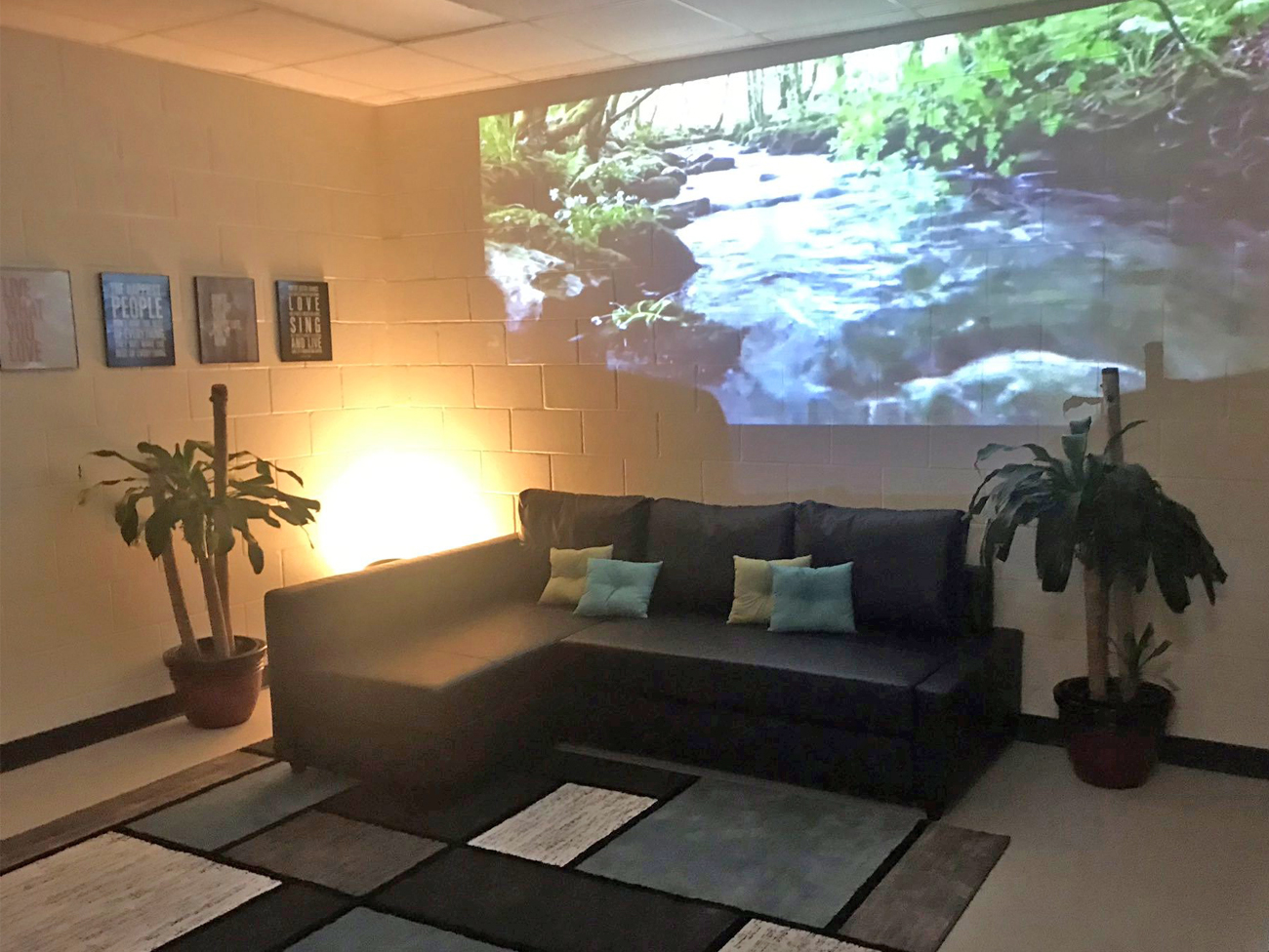 The McNair Mindfulness Mansion includes a sofa, two relaxation chairs, a projector displaying an image of a stream on the wall,