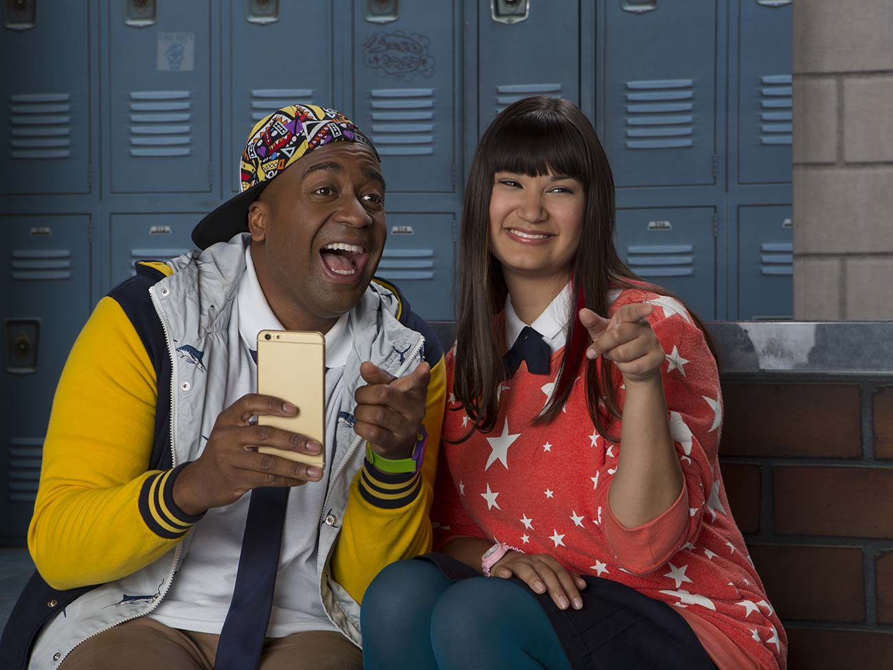 young man and woman sitting in high school hallway pointing and laughing