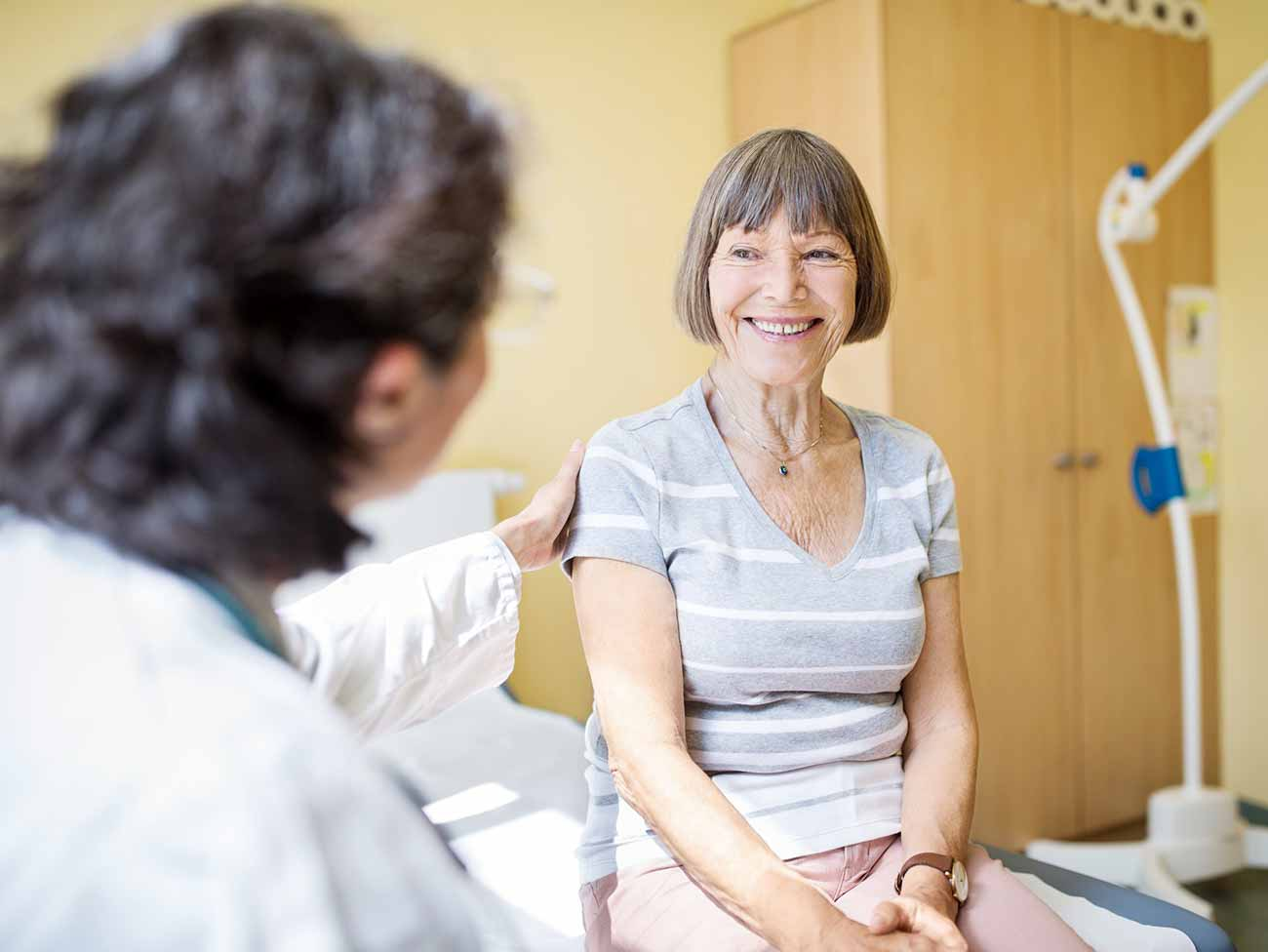 A senior woman smiling senior at her physician during an exam.