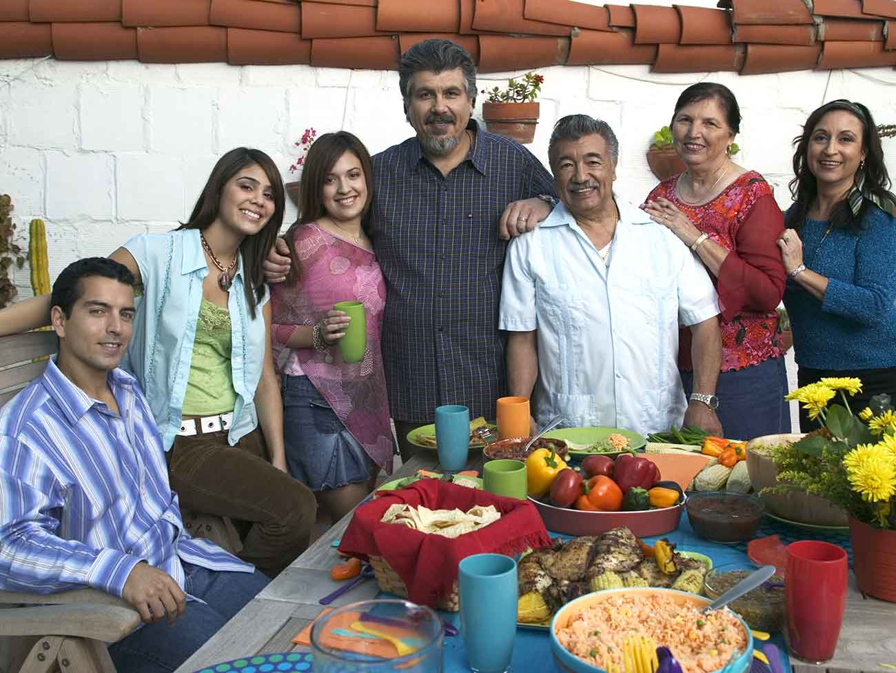 A large, happy Hispanic family smiling at the camera.