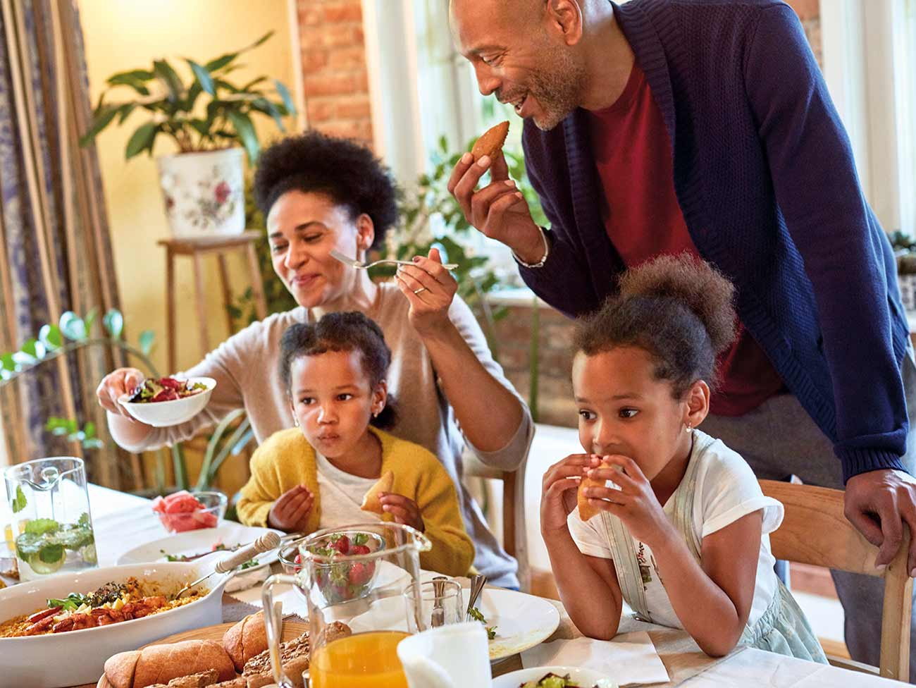 A happy family seated at a table filled with a holiday feast.