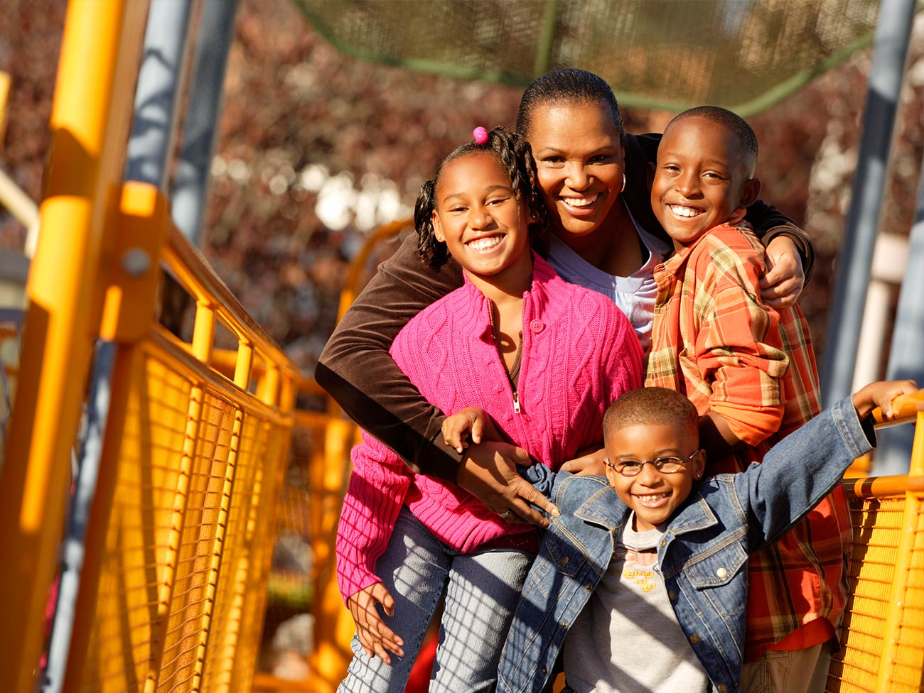 African American woman and her kids on a yellow bridge
