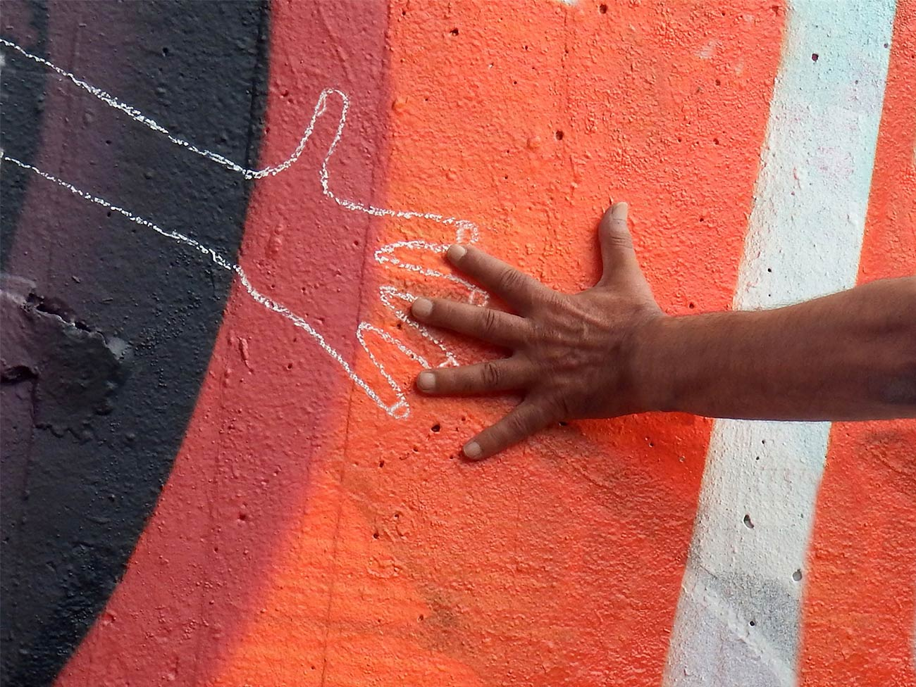 Hand reaching out to chalk outline of a hand on a colorful wall