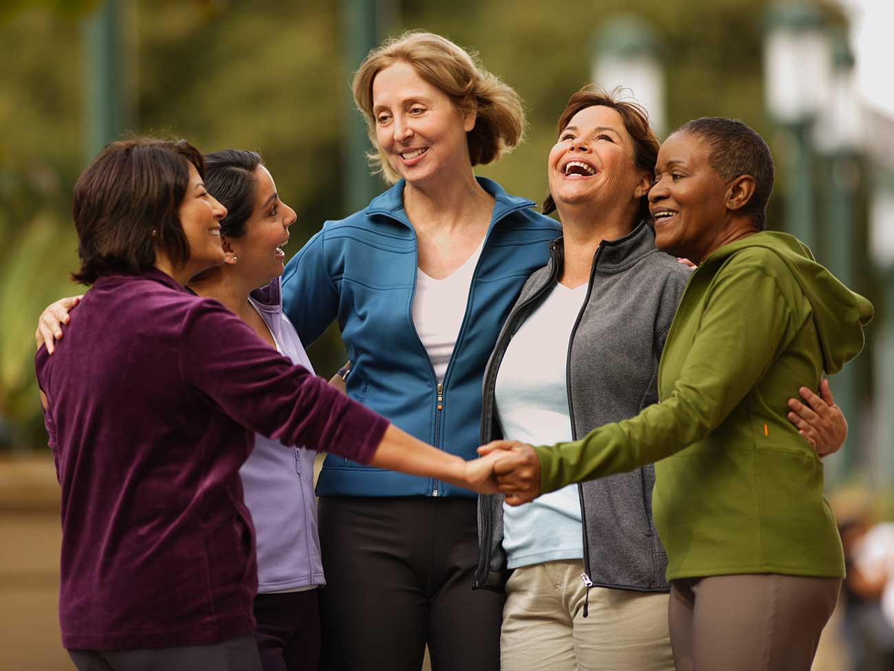 Group of 5 laughing women, standing in a circle with hands joined.