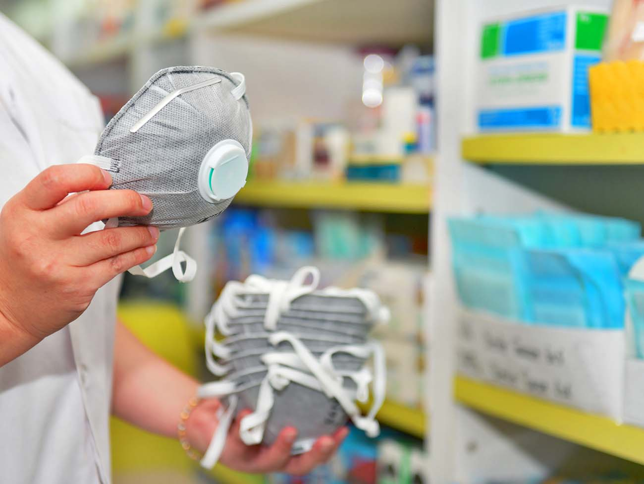 Pharmacist hand holding N95 mask in pharmacy drugstore
