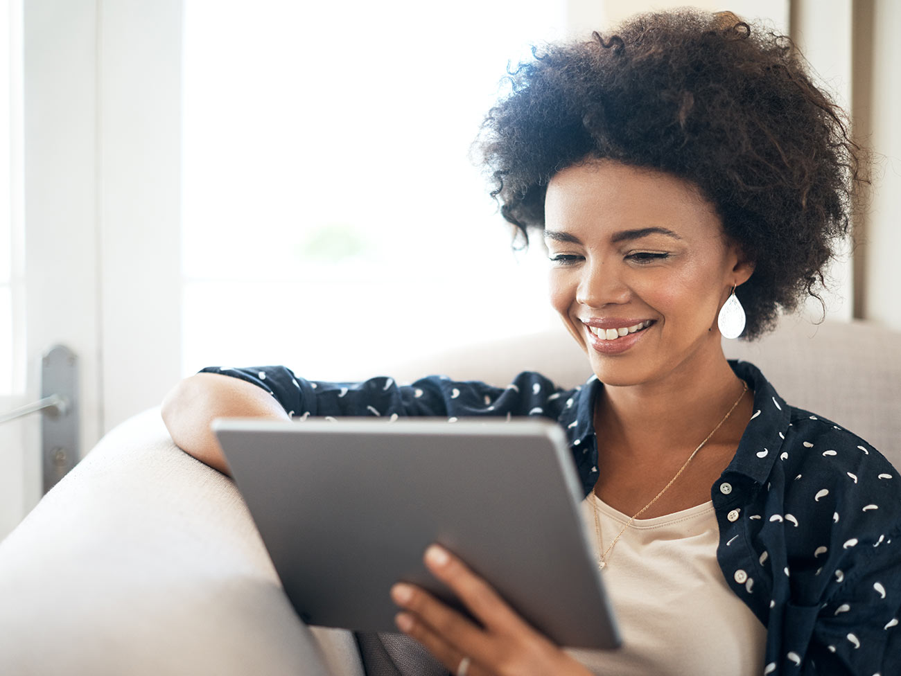 woman sitting on sofa looking at her tablet computer and smiling