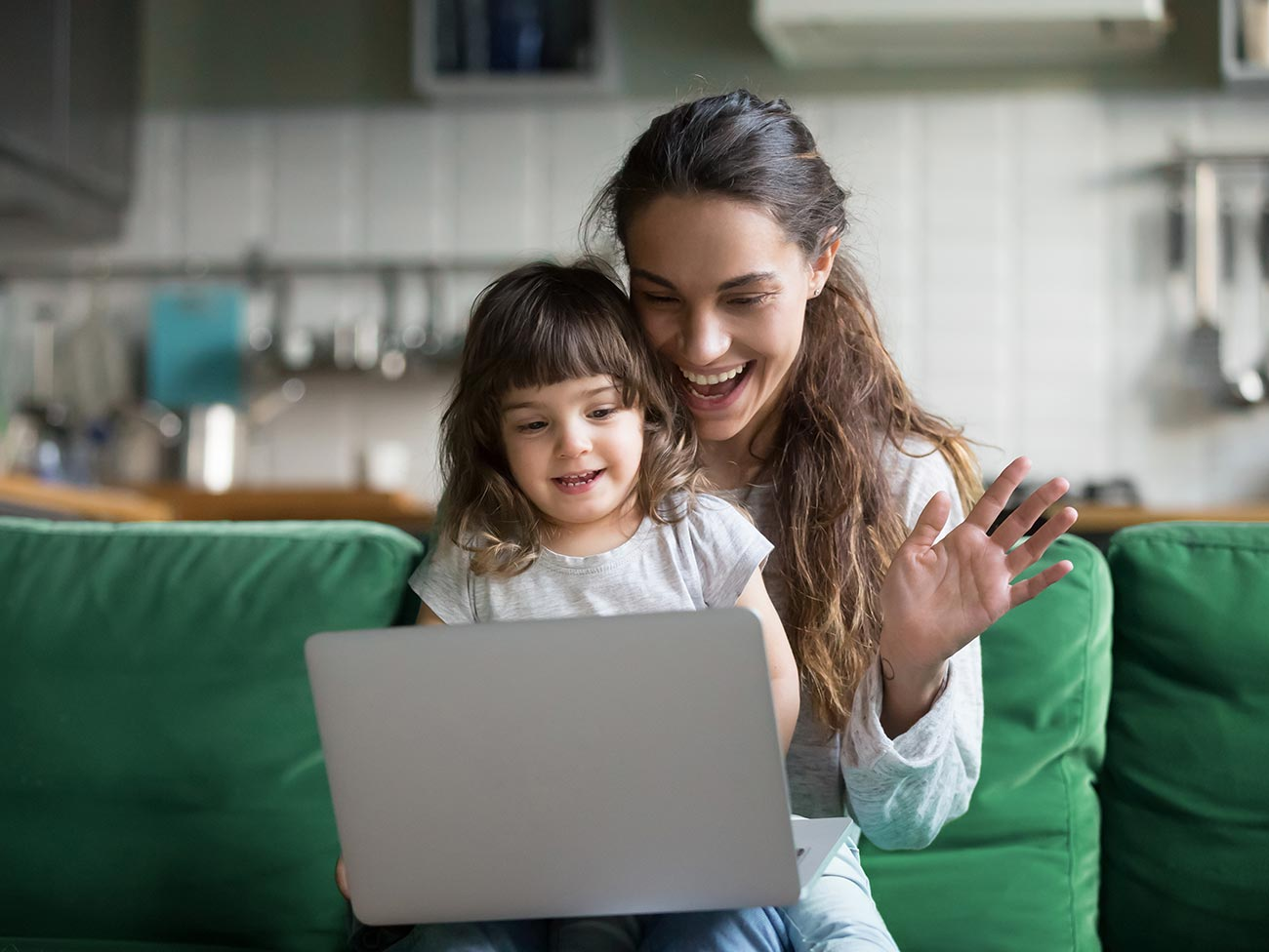 woman with young girl looking at laptop computer and smiling