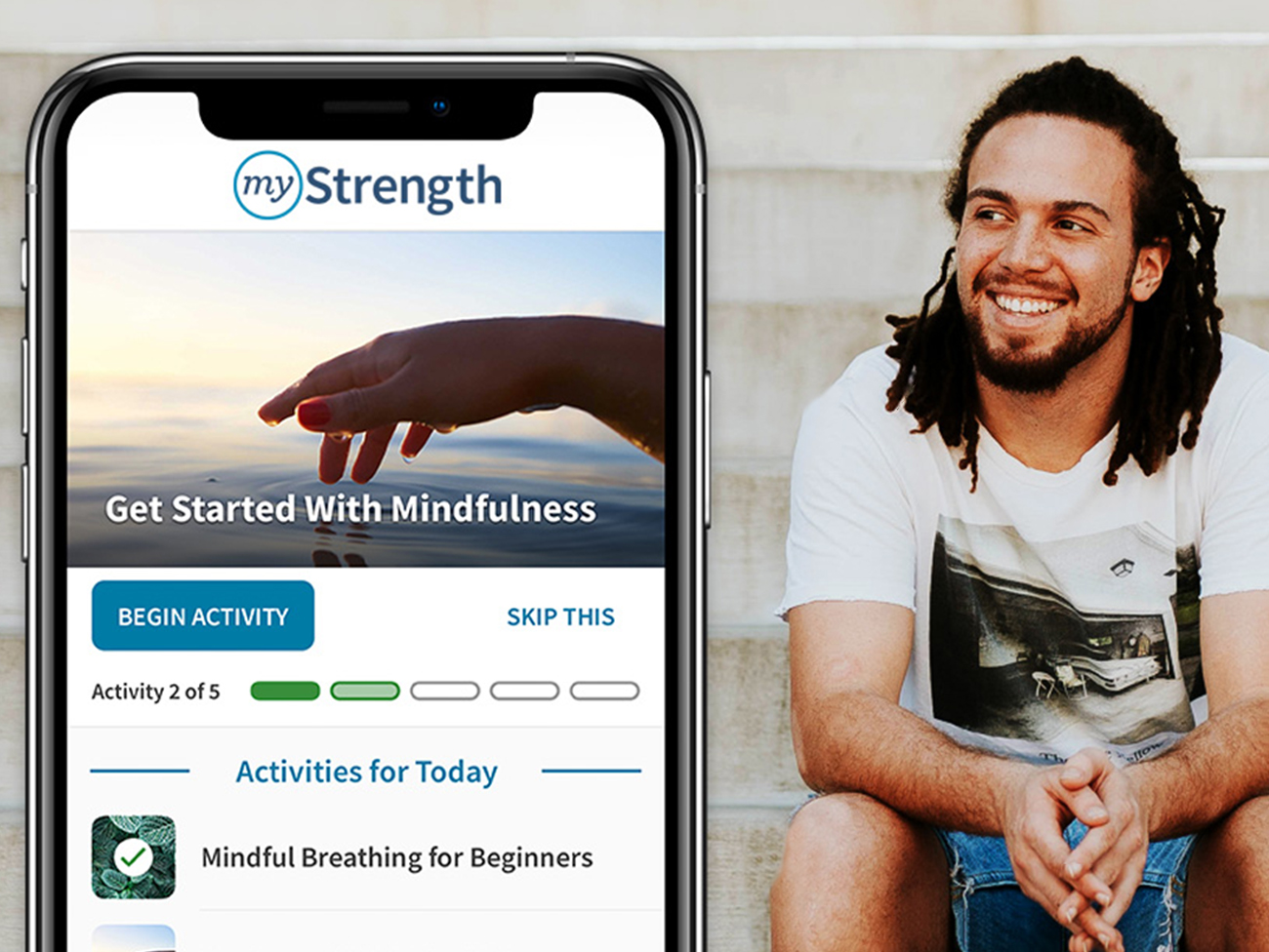 A mobile phone with the Kaiser Permanente myStrength app loaded and an image of a smiling young man sitting on some steps.