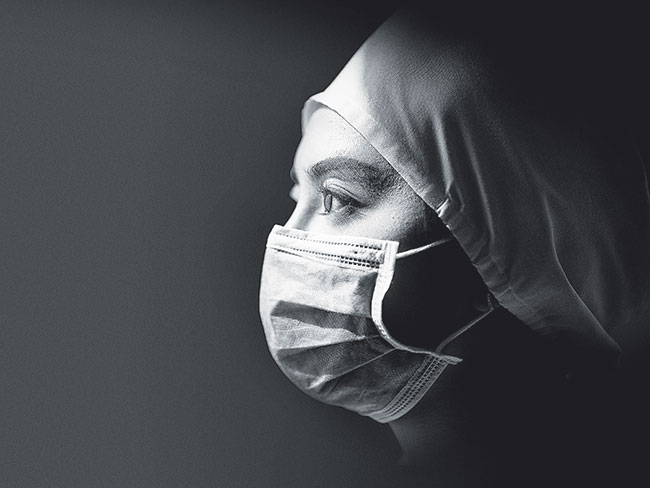 Black and white profile image of a female nurse in a cap and face mask.
