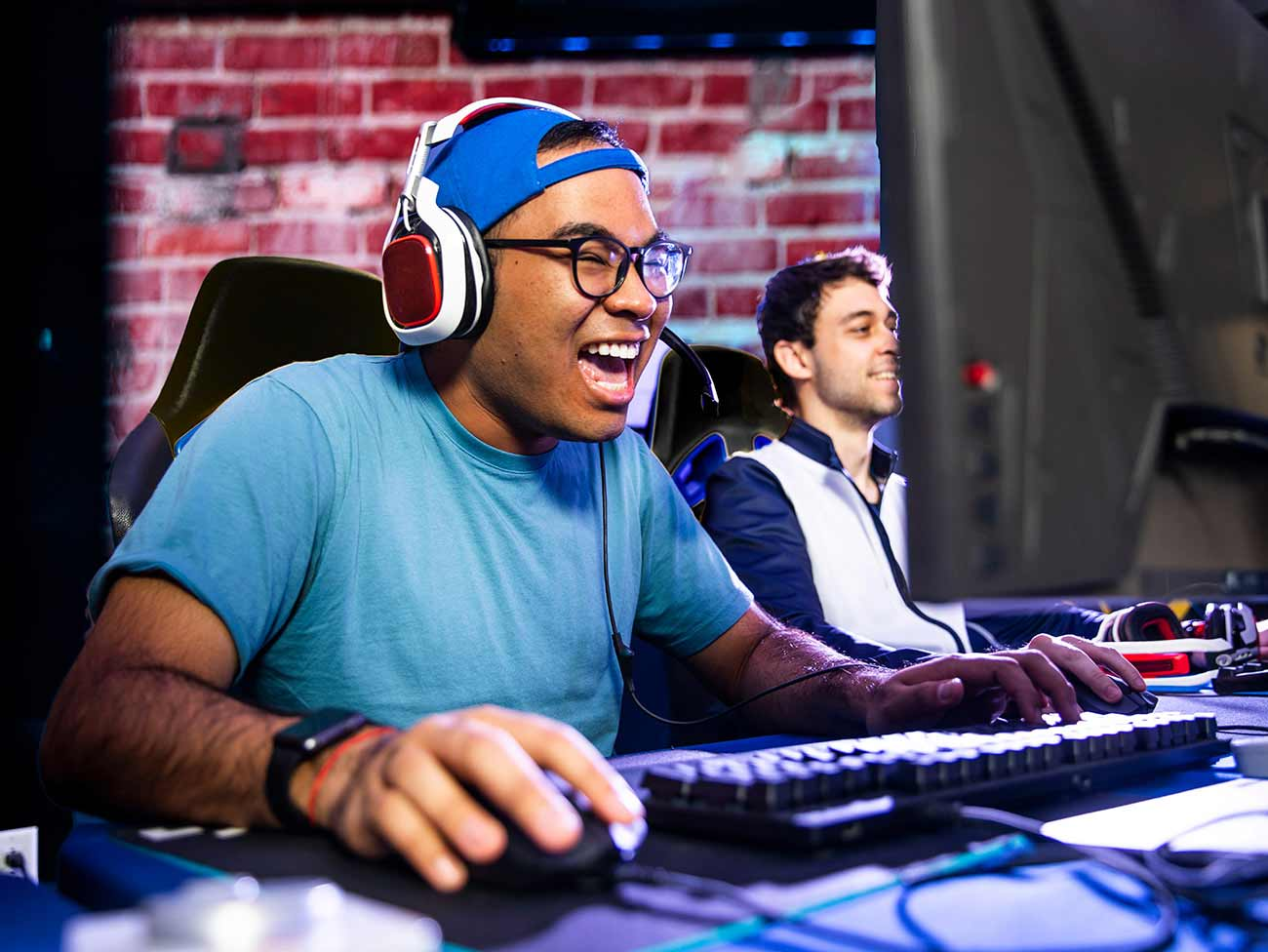 Young man reacts enthusiastically as he plays a video game at a desktop computer