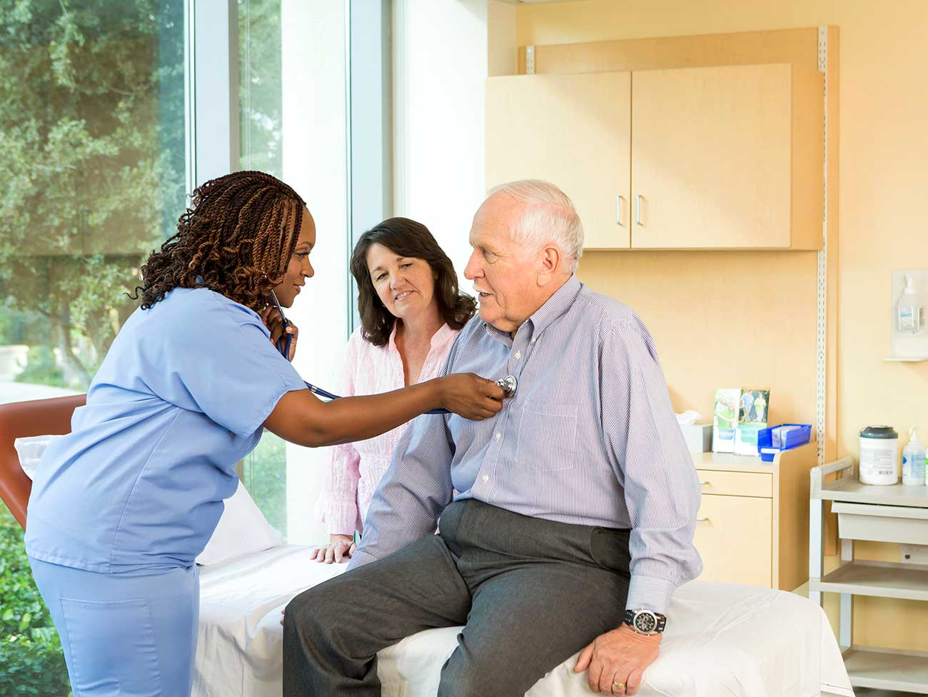woman medical care worker listening to the heartbeat of an elderly man