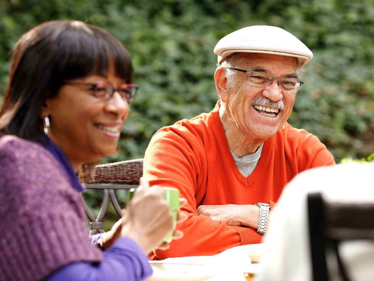 A multi-cultural group of smiling seniors, seated around a table outdoors.