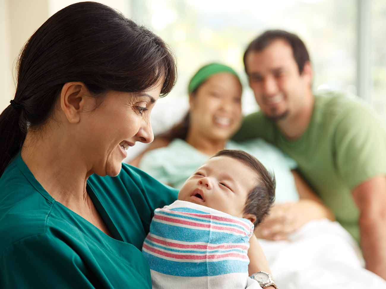 Nurse holding a newborn baby with smiling parents in the background