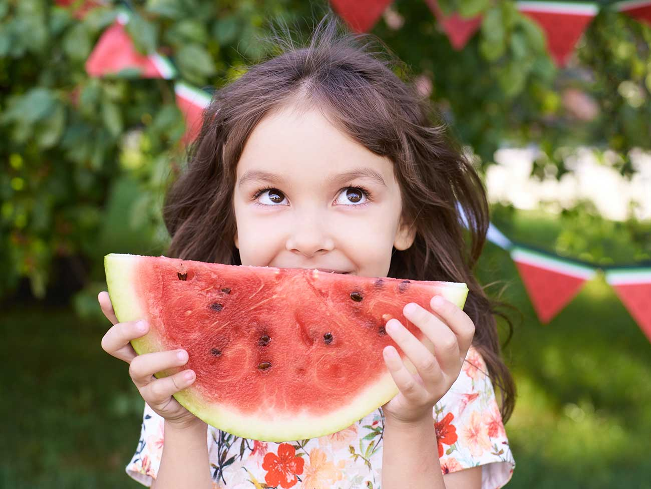 A smiling, young girl eating a huge slice of watermelon.