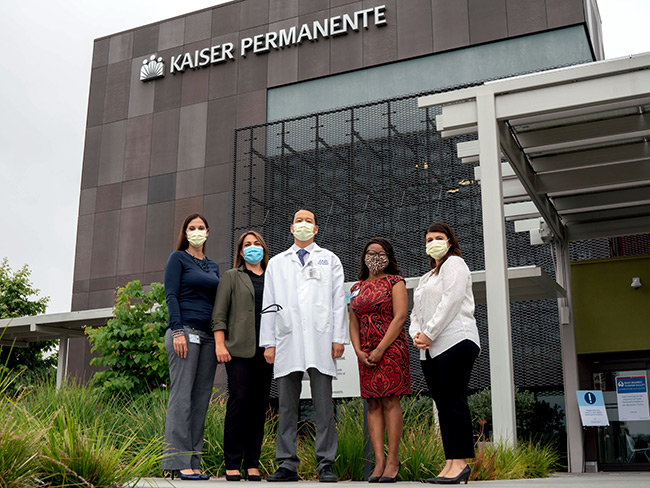 Group of physicians and employees wearing face masks, standing in front of a Kaiser Permanente hospital.