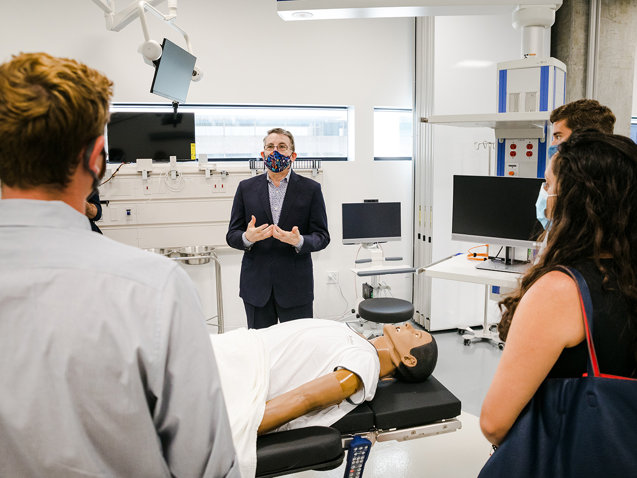 Mark Schuster, MD, PhD, founding dean and chief executive officer, leads students from the school's inaugural class on a tour of the simulation lab.