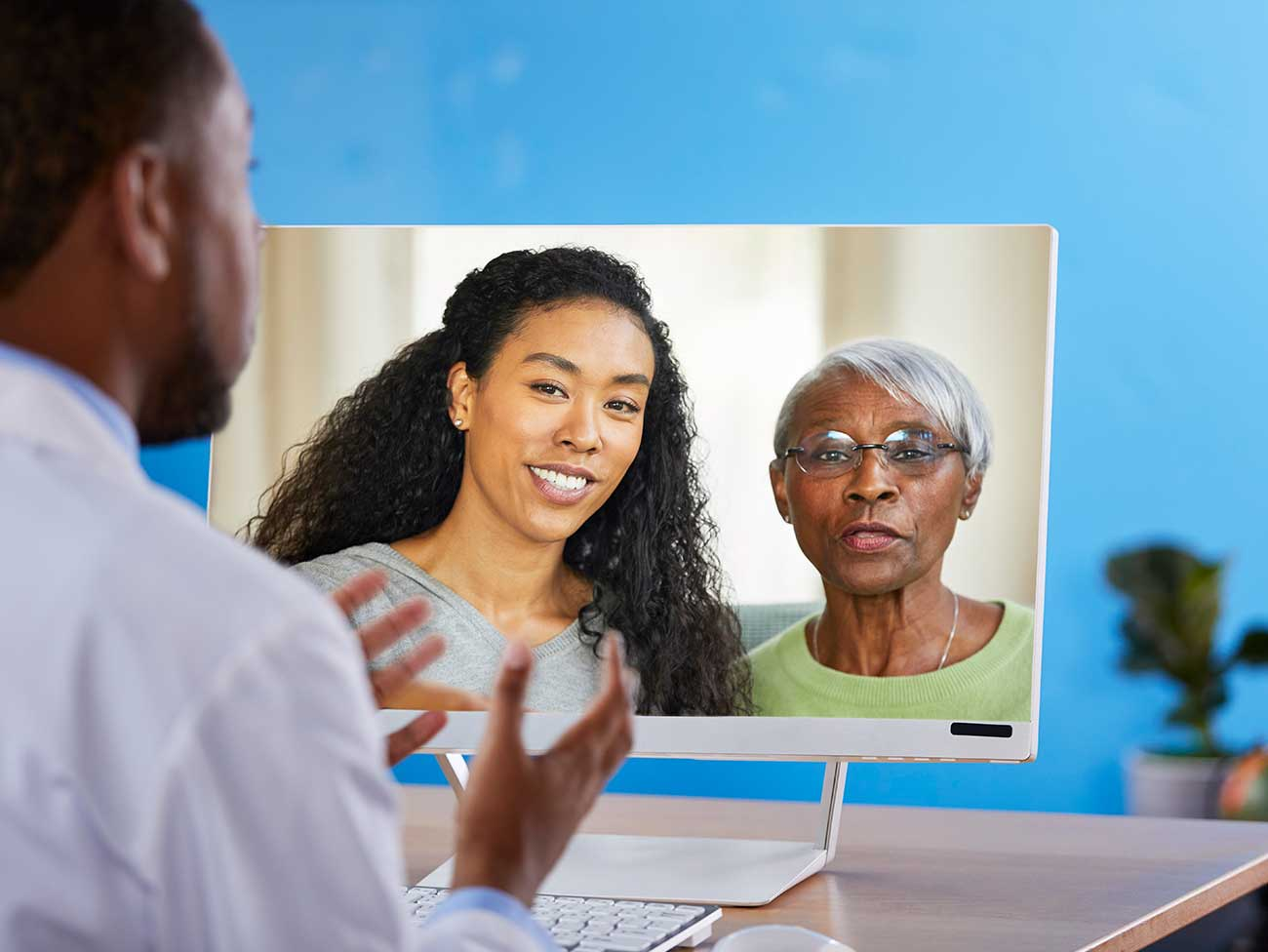 Male physician chatting with a woman and her mother over video chat on a computer screen