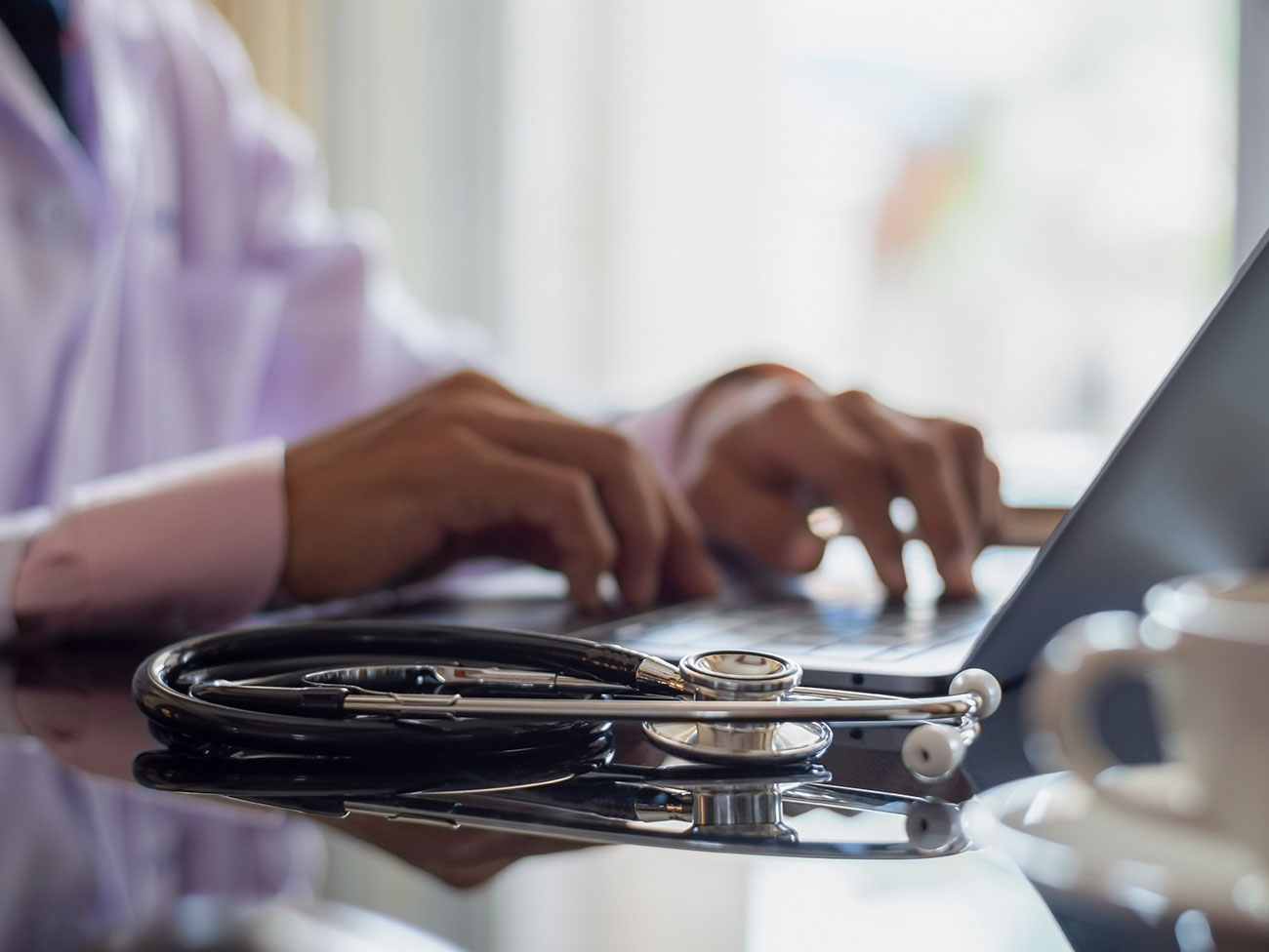 hands of a medical professional on the keyboard of a laptop