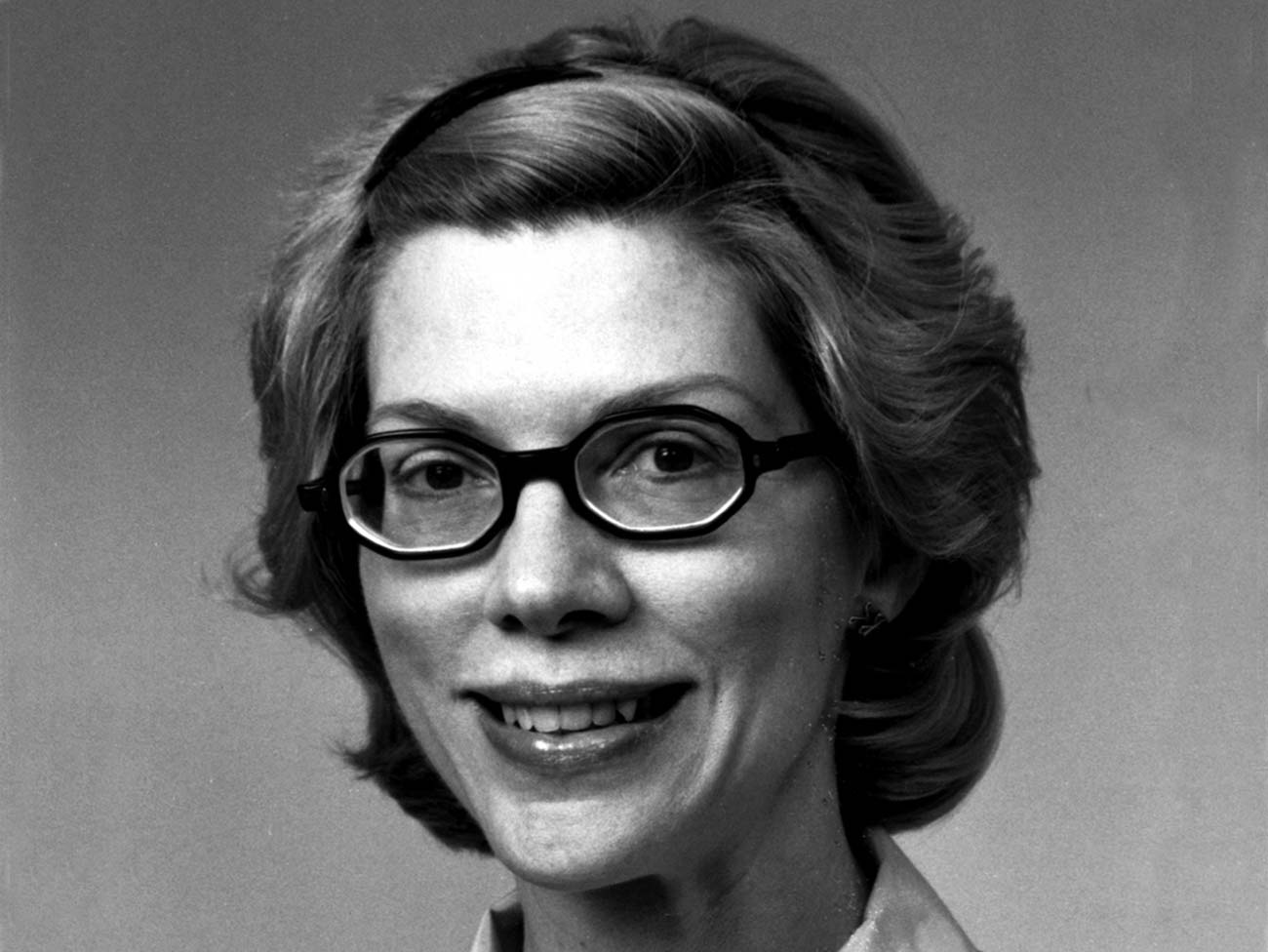 black and white photo of a woman smiling and wearing glasses