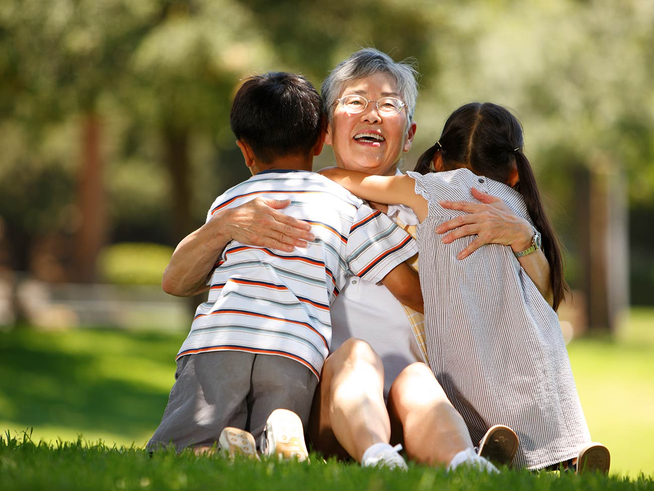 Senior woman hugging her grandchildren while sitting on the grass