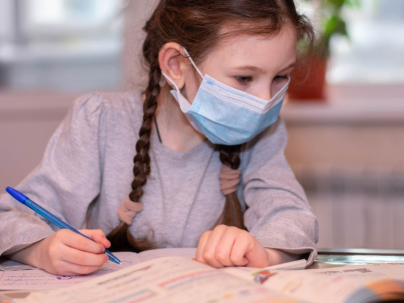 young girl wearing face mask seated at table doing schoolwork