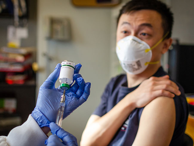 An Asian-American man wearing a face mask watching a physician draw a vaccine from a bottle with a needle.