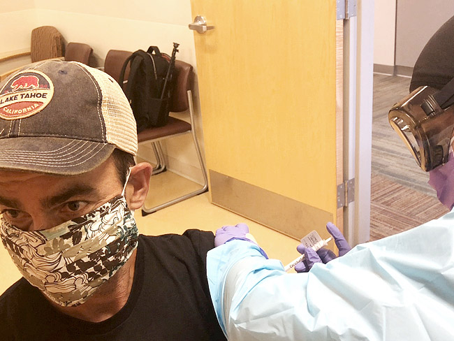 man wearing face mask receiving vaccine injection