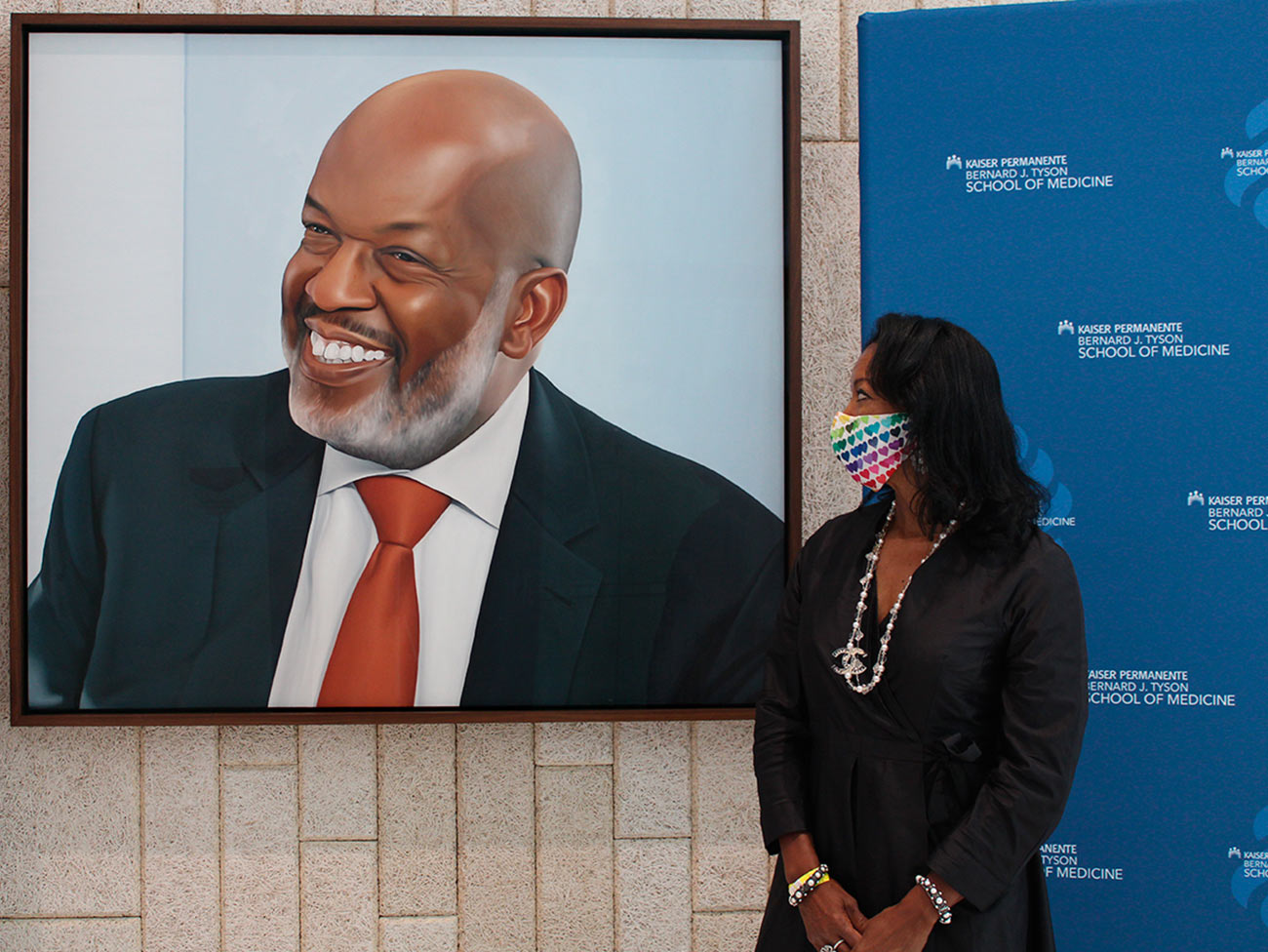 Denise Bradley-Tyson admiring a portrait of Bernard J. Tyson at the Kaiser Permanente Bernard J. Tyson School of Medicine