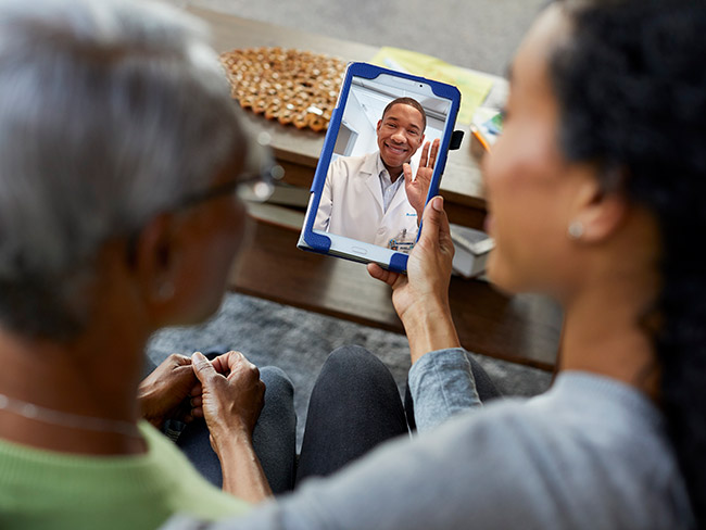 Over the shoulder shot of two women sitting together during a telehealth visit on a mobile phone with a male physician who is smiling and waving.