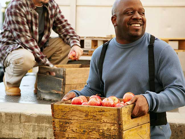 Smiling Black man carrying a crate of apples.