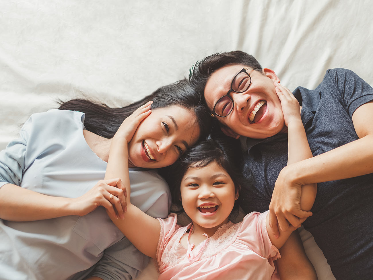 Asian family smiling and laughing on a bed