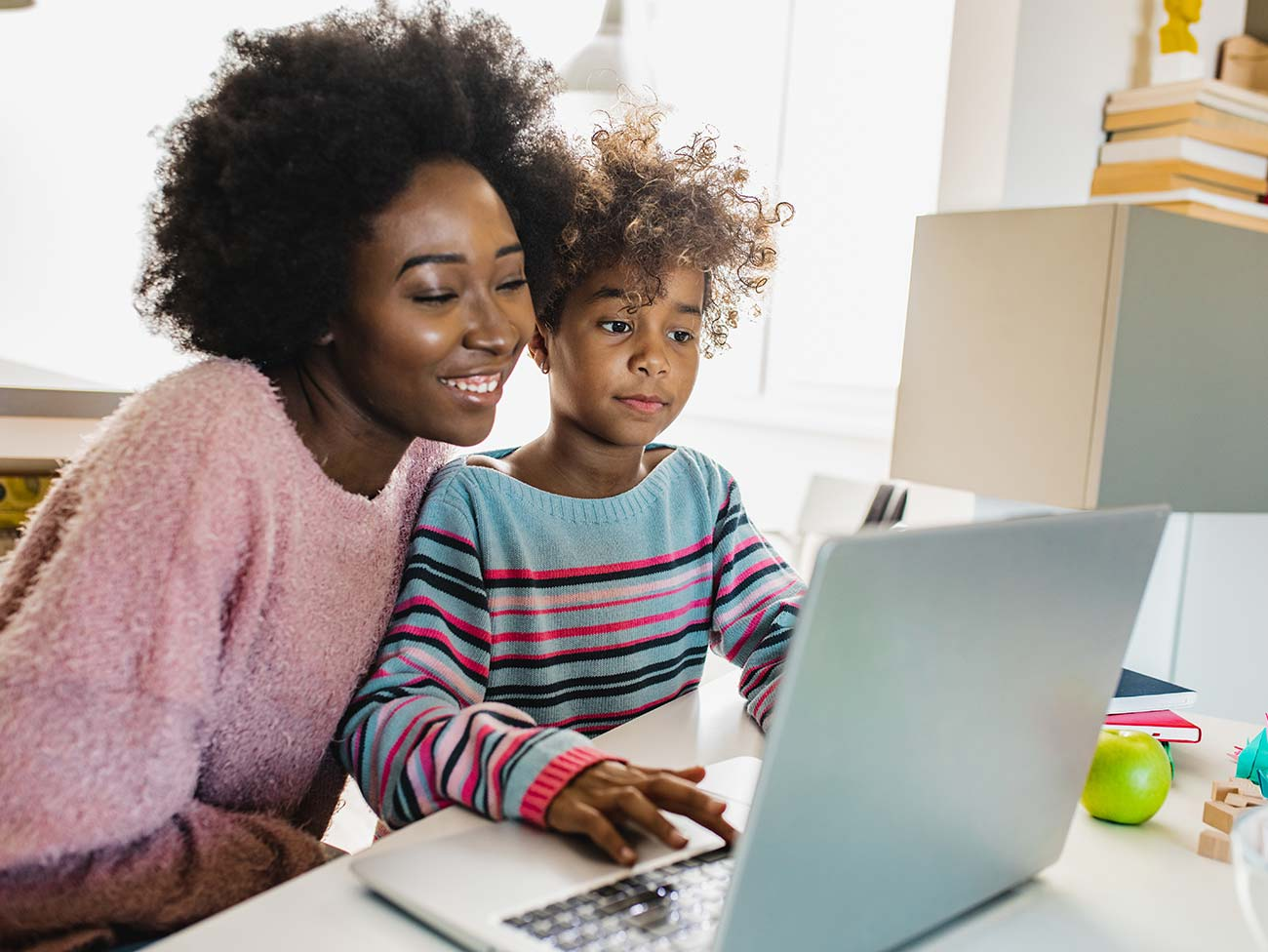 Black mother helping her daughter with school work at home on a laptop