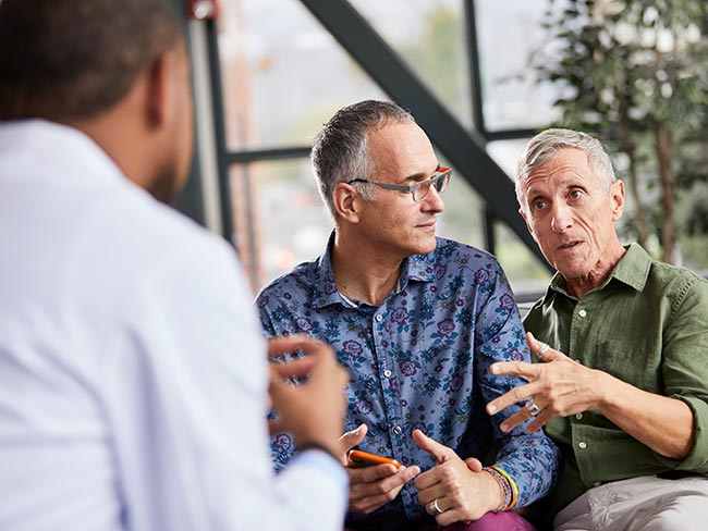 A male couple sitting together, consulting with a male physician.