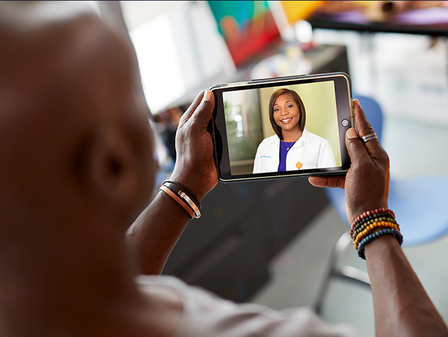 An over the shoulder shot of a man speaking to a smiling female physician during a telehealth visit.