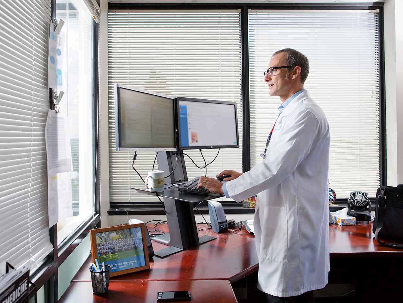 man wearing a white doctors coat standing at a computer with dual monitors