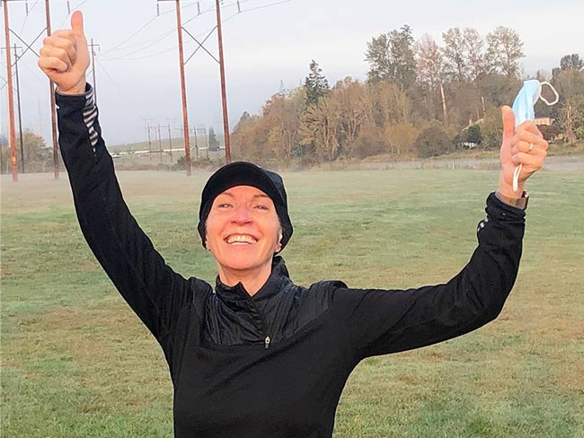 "woman in an outdoor field dressed in athletic clothing smiling with arms lifted and hands doing the ""thumbs-up"" sign"