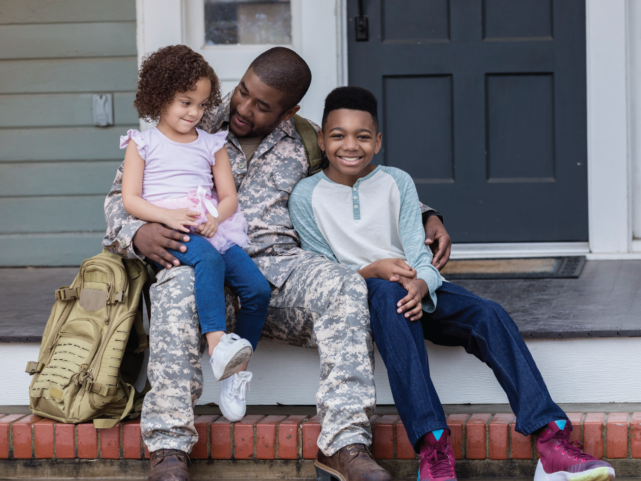 man wearing camouflage military fatigues seated on porch with 2 young children