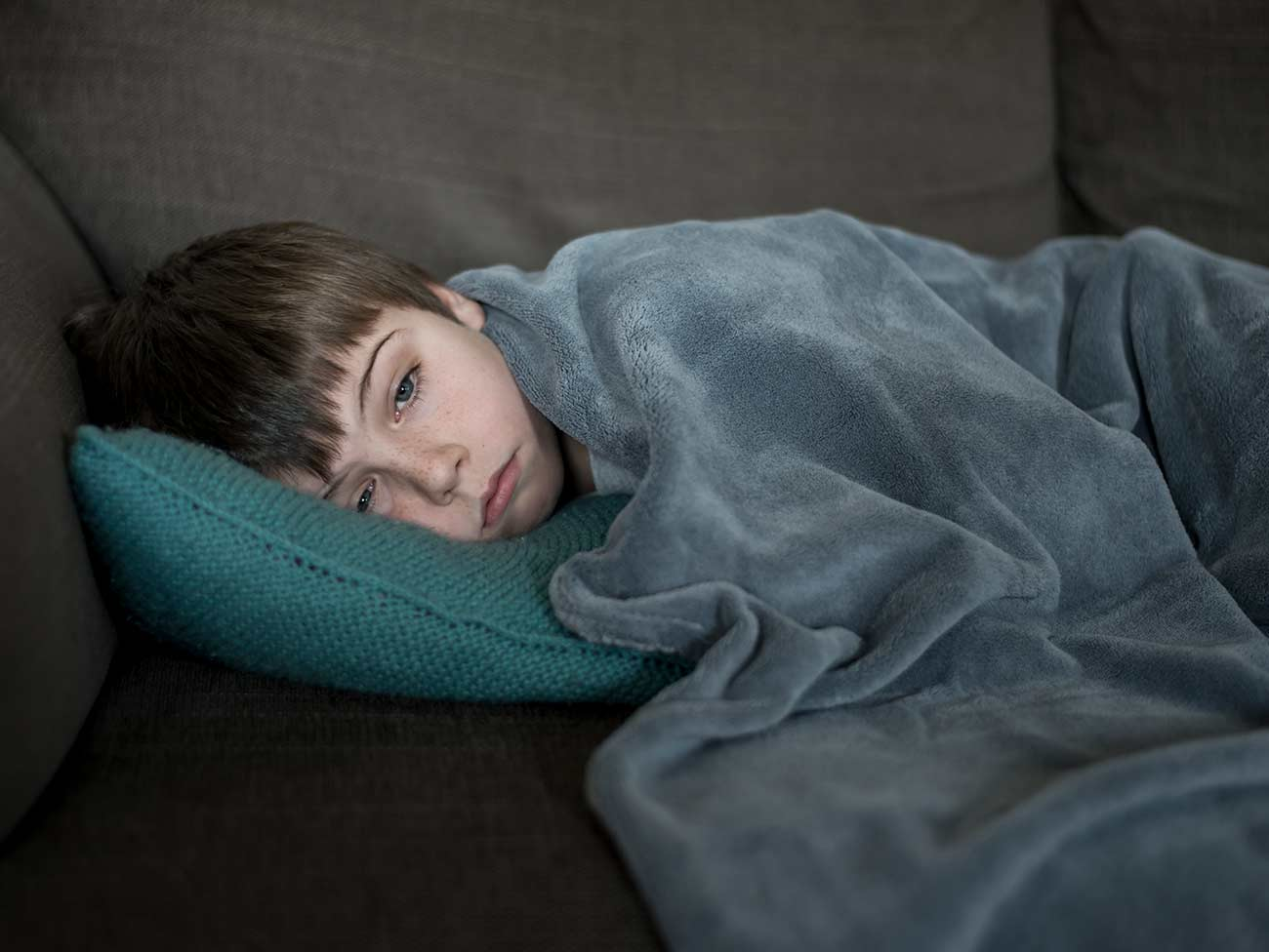 Boy with his head on a pillow under a blanket
