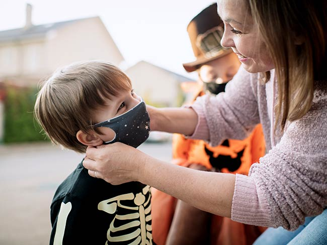 Mother putting protective face mask on her child during COVID-19 pandemic on Halloween.