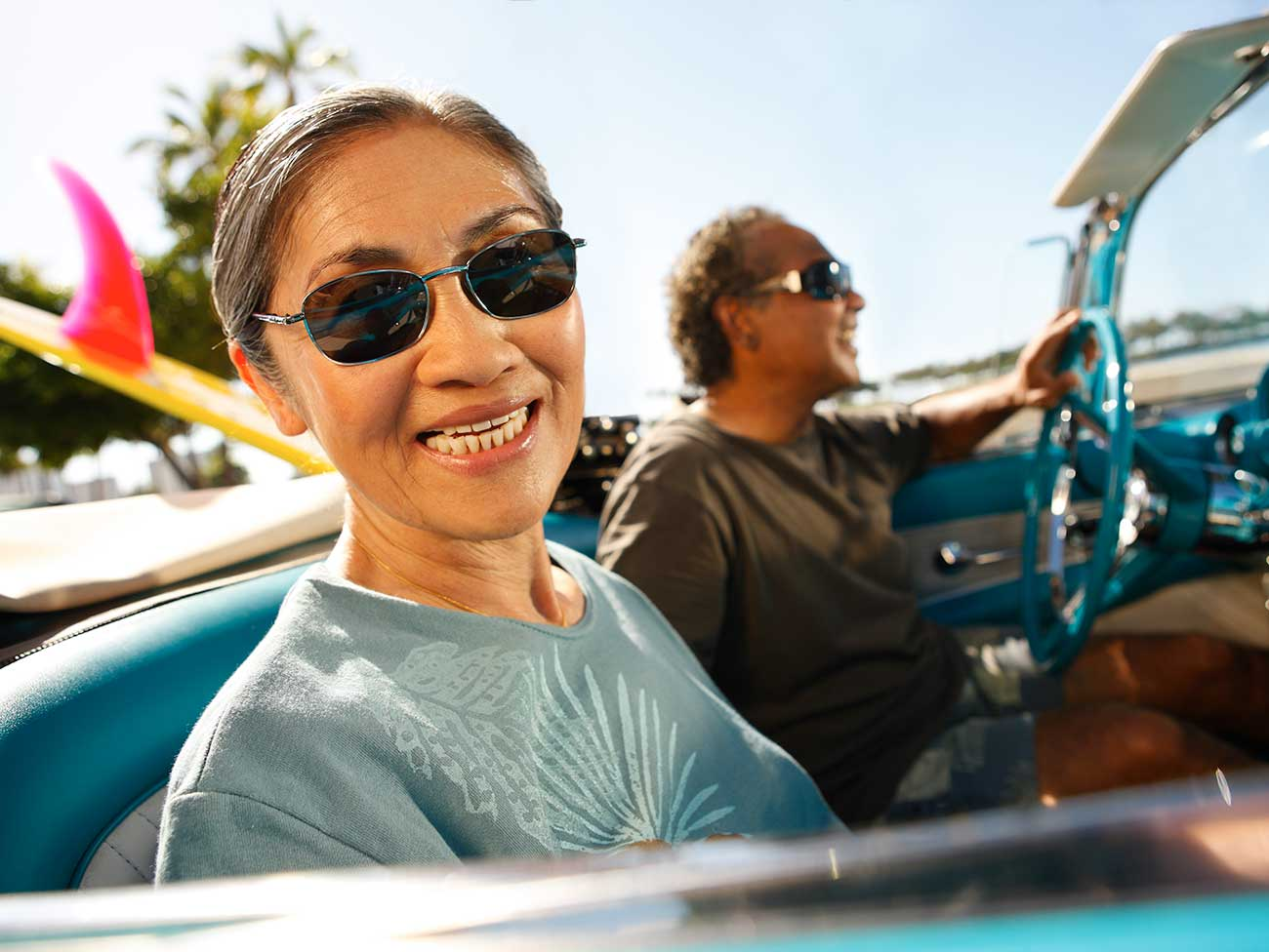 Woman and man riding in a convertible with a surfboard in the back seat