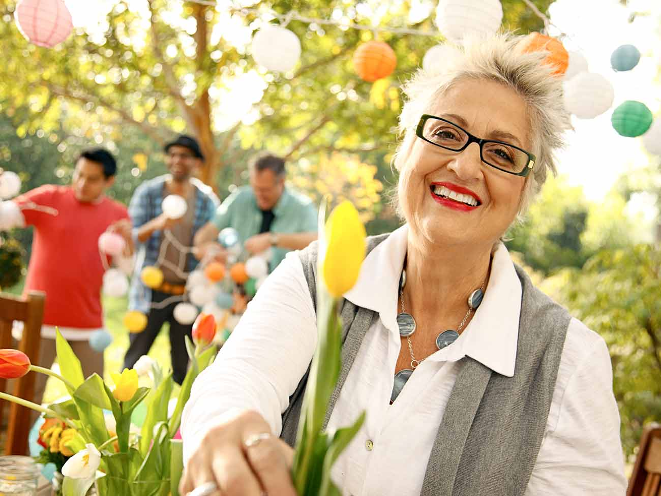 older woman outside in a party setting holding a yellow tulip flower
