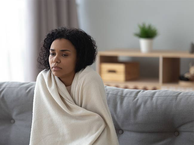 Sick woman wrapped in a blanket, sitting on a couch.