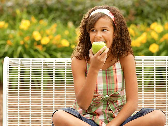 A smiling teenaged girl biting down into a green apple.