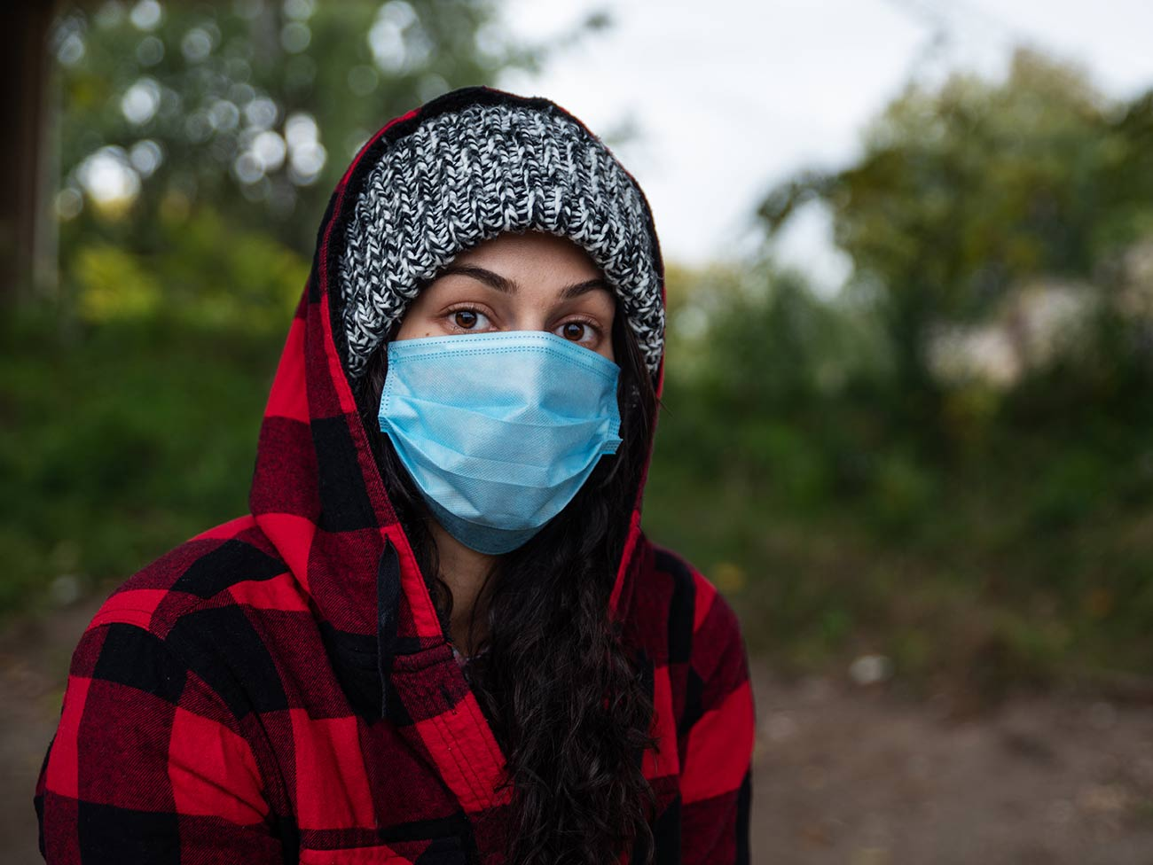 young woman outdoors wearing hooded flannel top and mask