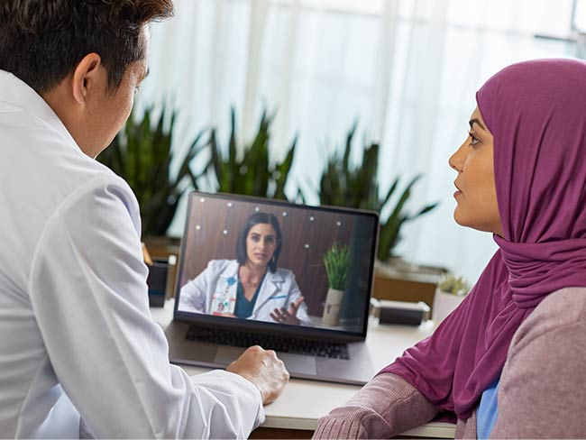 man and woman seated in front of computer screen with video call to physician